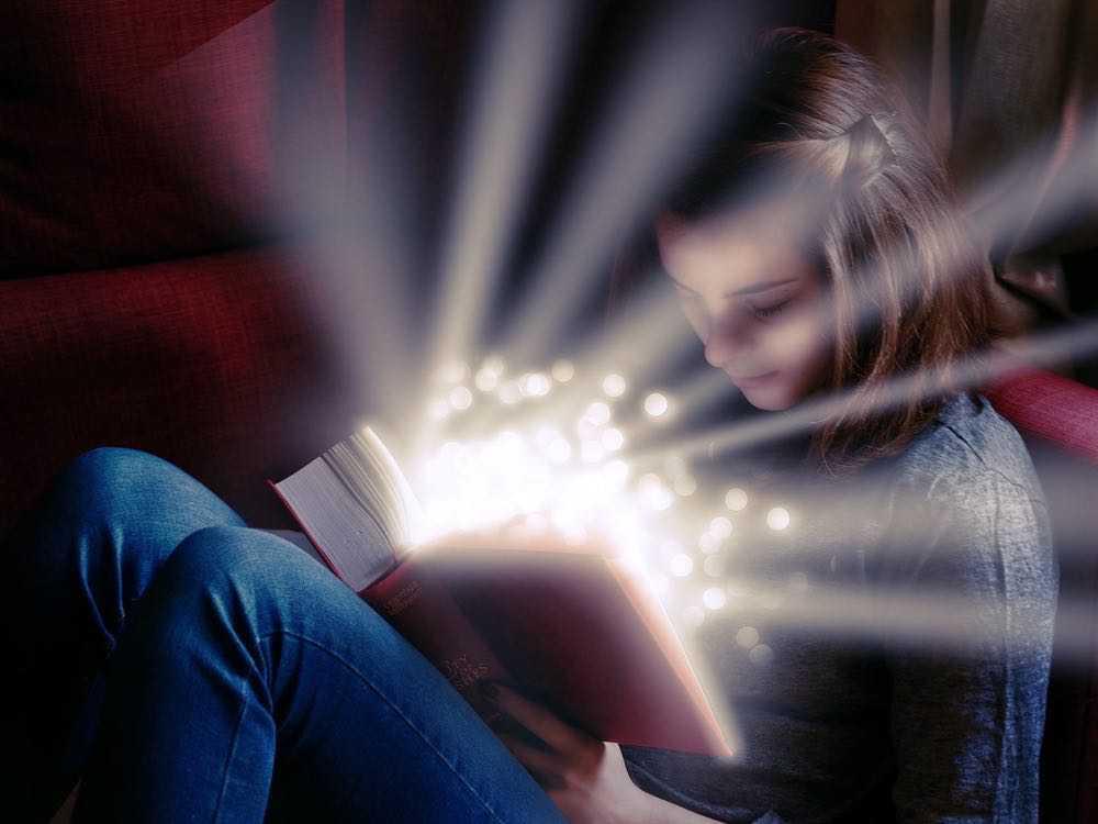 ado assis parterre lisant un livre d'où une lumière s'échappe