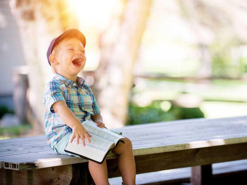 un enfant handicapé assis sur une table de pique-nique rit aux éclats avec un livre sur les genoux